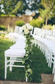 White Ceremony Chairs With Green And Floral Decorations