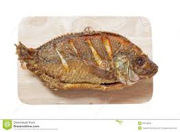 Deep Fried Tilapia Fish On Wooden Chopping Block Isolated