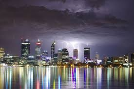 A Series Of Bolts Lightning Strike The Brightly Lit Perth Skyline At Night With