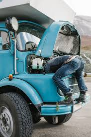 Male Mechanic Repairing Old Truck In A Funny Way | Stocksy United