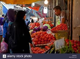 iranian muslim women wearing scarves buying vegetables and red