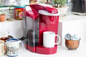 A Red Keurig Coffee Machine On White Kitchen Counter Surrounded By Mugs