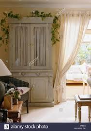 creme land wohnzimmer mit pastell grün bemalten schrank