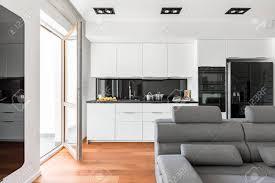 modernes wohnzimmer mit sofa balkon und weißer offener küche