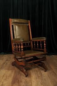 Early 20th Century American Rocking Chair With Green Rexine Upholstery.