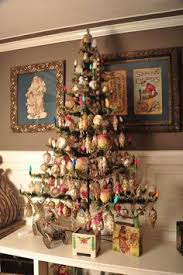 A Feather Tree With Antique Glass Ornaments And Christmas Wood Puzzle Beneath The