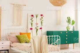 weiße handgefertigte macrame über einem metallbett mit bunten kissen und gezackten betten im modischen bohoschlafzimmerinterieur mit grünem schrank