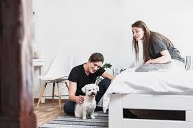 junger mann und frau die ihren hund im schlafzimmer