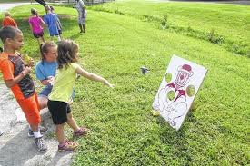 Kids Are Taught To Encourage One Another While Playing A Bean Bag Toss