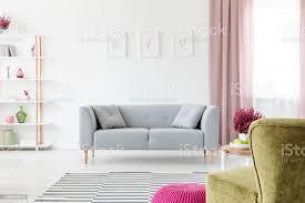 lounge mit kissen platziert in echtes foto weißen wohnzimmer interieur mit plakaten an wand grau schmutzig rosa vorhänge am fenster rack mit