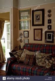 gruppe bildern an der wand über dem sofa mit tartan