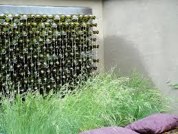 Interesting Use Of Recycled Bottles For Garden Wall Art