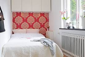 Narrow Bedroom With Pink Wallpaper And Overhead Cabinet Storage Sheepskin Rug