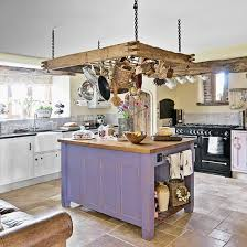 Rustic Kitchen With Ceiling Hung Pan Rack And Purple Island