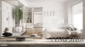 vintage holztisch regal mit stein balance und 3d buchstaben das wort fengshui über minimalistisches schlafzimmer und badezimmer mit dusche und