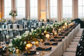 Long Wedding Reception Head Table With Green And White Floral Garland Candles Placesetting