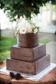 A Chocolate Wedding Cake With Rustic Woodcut Design Pinecone Decorations And White Floral