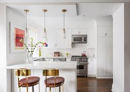 small white kitchen with mini brass and glass pendant lights
