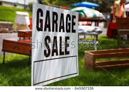 Garage Sale Sign On The Shady Lawn Of A Suburban Home Shallow Focus In Center