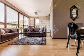 gemütliches braunes wohnzimmer mit sofas und couchtisch aus glas