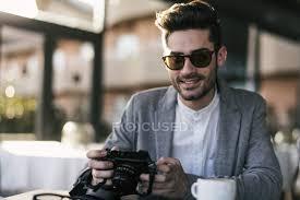 si e de bar giovane che si siede al bar con la macchina fotografica foto stock