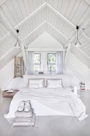 All White Bedroom Beneath The Vaulted Ceiling