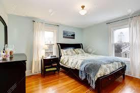 lgiht blaue schlafzimmer mit zwei fenstern und parkett mit schwarzen möbeln satz möbliert