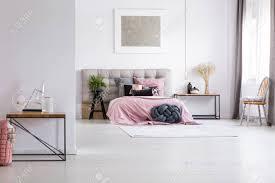 glasaccessoires auf tisch im geräumigen schlafzimmer mit silberner bemalung über bett mit rosafarbener auflage und schwarzen kissen