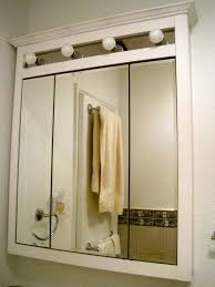medicine cabinet with mirror and light house decorations