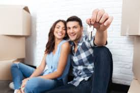Young Couple Holding Keys With Moving Boxes Behind Them