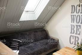 sofa mit grauen flauschig weichen teppich bettwäscheabdeckung gemütliches zimmer unter dem grauen dach und fenster in der decke hygge loft design