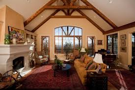 Cathedral Ceiling Ideas And Rustic Living Room Design With Wooden Exposed Beams White Mantel Fireplace Ethnic Red Area Rug Brown Slipcover Sofa