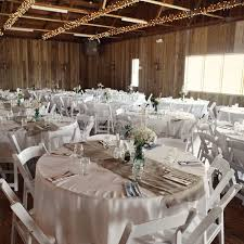 Rustic Country Wedding Reception Decorations With Small Flowers On Round Tables And Wooden Folding Chairs