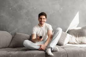 foto freudigen mann 30er jahre in freizeitkleidung sitzt auf sofa in li foto vadymvdrobot auf envato elements