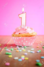 Number one birthday candle on a pink cupcake on a wooden table Stock