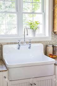 küche interieur mit rustikalem weißem porzellan waschbecken und granit arbeitsplatte unter großen sonnigen fenster