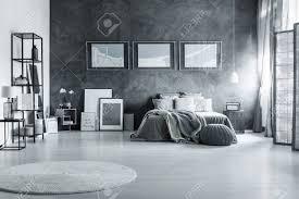 graues schlafzimmer mit trennwand strukturierter wand regal poster und anhänger im dachboden