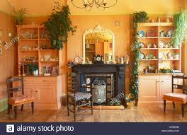 Antique Chairs And Painted Dressers On Either Side Of Black Victorian Fireplace In Pale Orange Dining