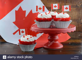 Happy Canada Day Celebration Cupcakes On Red Cake Stand With And White Maple Leaf Flag Against A Rustic Distressed Wood Back