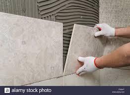 laying ceramic tiles tiler puts tile adhesive on the wall stock