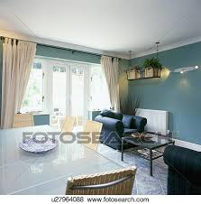Glass Table And Wicker Chairs In Green Blue Dining Room With Cream Curtains At Patio Doors