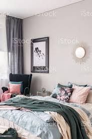 sonnenform wie spiegel und karte in schwarzem rahmen auf graue wand der modischen schlafzimmer interieur mit kingsizebett mit gemütlichen bettwäsche