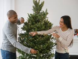 Couple Stringing Lights On Christmas Tree