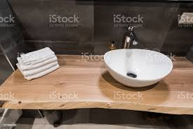 modernes interieur des badezimmers das waschbecken besteht aus weißen schale auf den tisch aus holz minimalismus und einfachheit in einem