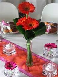 red gerbera daisies inside a clear glass bowl lined with a few