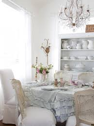 dining table with white tablecloth and white wooden chairs also