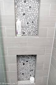 two shower nooks with marble pebbles and horizontal grey porcelain