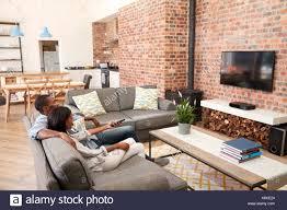 paar auf sofa in offenes wohnzimmer vor dem fernseher sitzen
