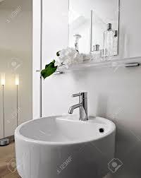 detial aus stahl wasserhahn für weißen runden waschbecken in einem modernen badezimmer