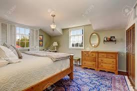 das gemütliche und komfortable atmosphäre im schlafzimmer mit holzmöbeln set und bunten teppich weiß französisch fenster machen den raum hell und